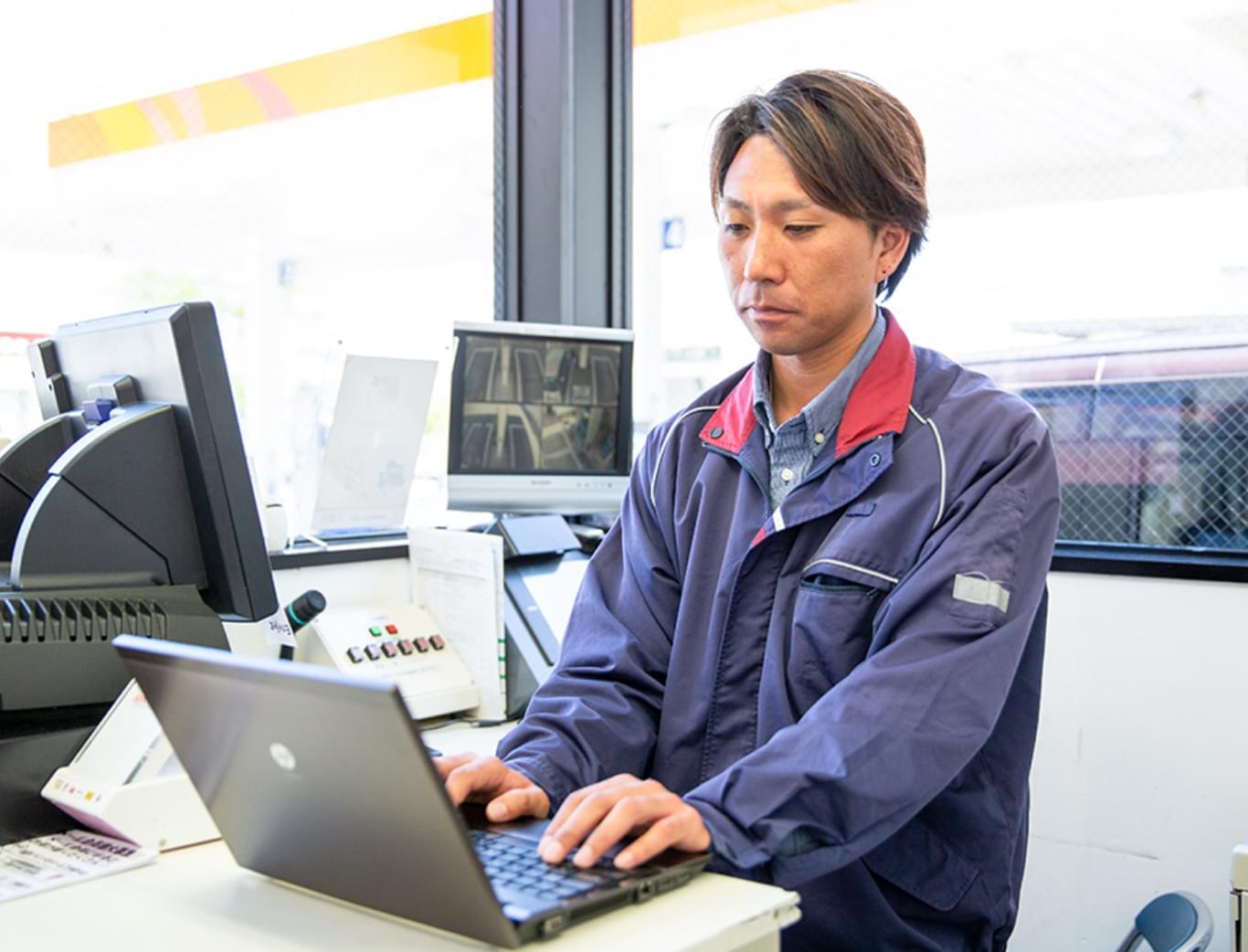 PCで作業をするガソリンスタンドのスタッフ